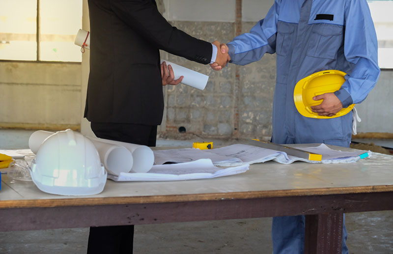 Individuals in consultation & using construction tools